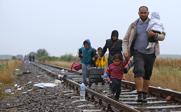 Migrants walk along rail track in rain from Roszke to Szeged in Hungary